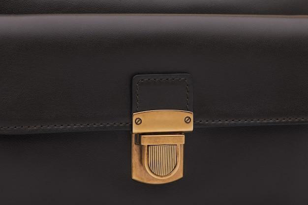 Fermoir de serrure d'or de luxe sur le sac en cuir noir, plan rapproché