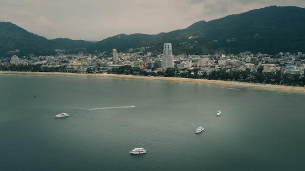 Les ferries de la vue aérienne flottent dans la mer et le fond de la montagne de la ville phuket thaïlande dans le style cinématographique de la saison des pluies
