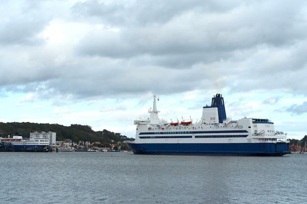 Ferry dans une baie avec port en arrière-plan