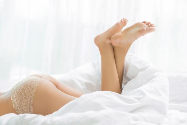Fesse d'une femme allongée sur son lit détendue.