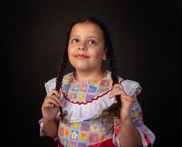Festa junina au brésil, fille brésilienne avec des tresses et habillée pour une fête junina faisant des poses.