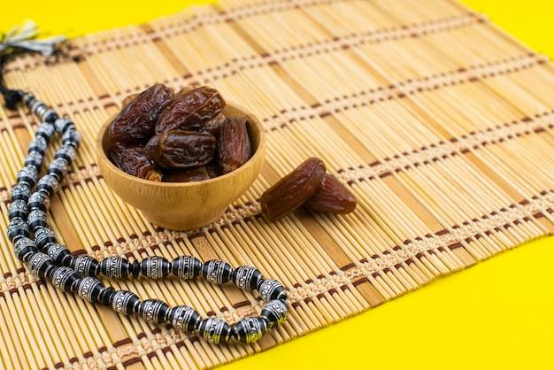 Festival du ramadan kareem. gros plan de dattes séchées fruits dans un bol en bois avec chapelet noir sur fond jaune. espace copie