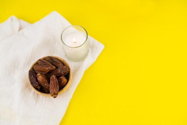 Festival du ramadan kareem. gros plan de dattes séchées fruits dans un bol avec bougie sur fond jaune. copiez l'espace.
