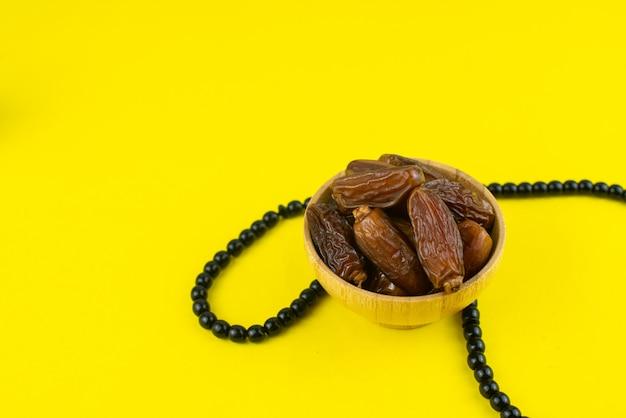 Festival du ramadan kareem. gros plan de dattes séchées fruits dans un bol avec chapelet sur fond jaune. copiez l'espace.