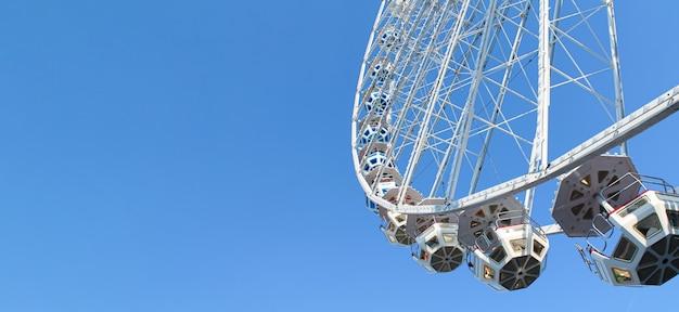 Festival grande roue sur fond de ciel bleu.