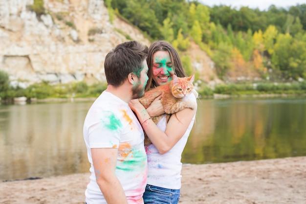 Festival holi, concept de tourisme et de nature - portrait de femme et d'homme avec un chat couvert de poussière multicolore.