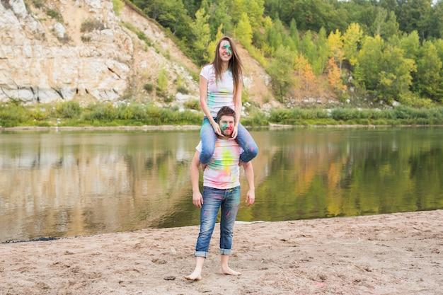 Festival holi, tourisme d'été et concept nature - jeune femme séduisante assise sur son petit ami sur la nature