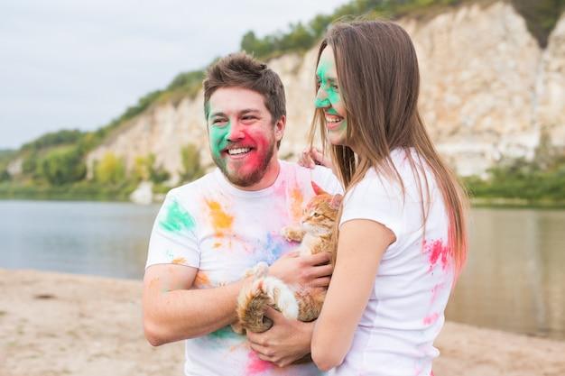 Festival holi, vacances, tourisme et concept nature - couple vêtu de chemises blanches tenant un chat et recouvert de poussière colorée.