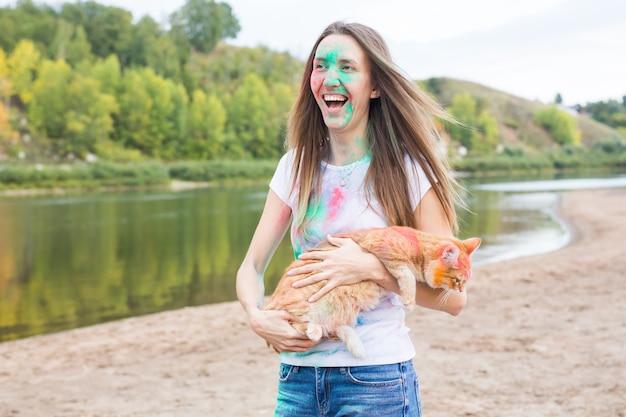 Festival holi, vacances, tourisme d'été et concept nature - jeune fille séduisante avec chat dans la poussière colorée sur fond naturel.