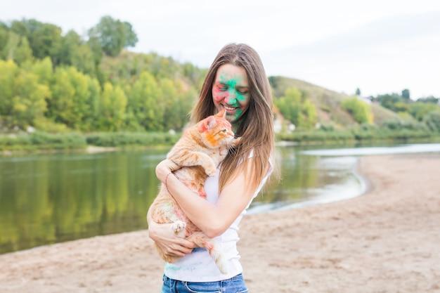 Festival holi, vacances, tourisme d'été et concept nature - jeune jolie jeune femme en peinture avec chat sur fond naturel.
