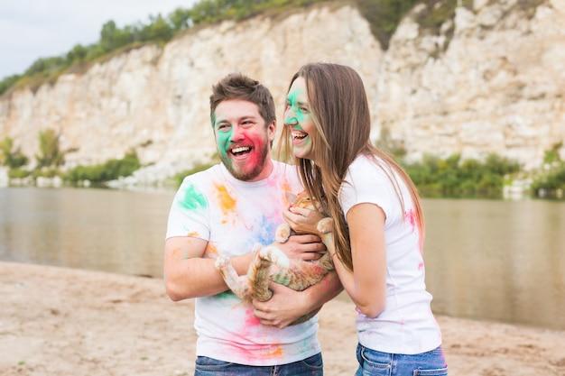 Festival holi, vacances, tourisme et nature concept - couple vêtu de chemises blanches tenant un chat et recouvert de poussière colorée