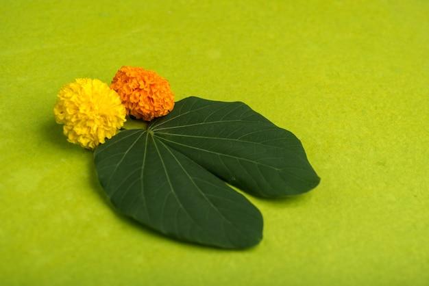 Festival indien de dussehra, montrant des feuilles d'or (bauhinia racemosa) et des fleurs de souci sur fond marron.