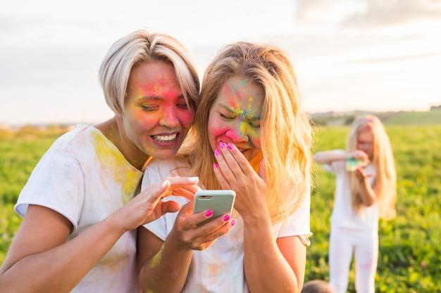 Festival indien de holi, concept de personnes - deux filles qui rient avec de la poudre colorée sur les visages regardent