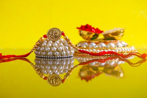 Festival indien raksha bandhan, rakhi avec des grains de riz, kumkum sur une assiette décorative, un bracelet indien traditionnel