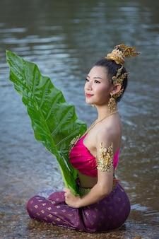 Festival loy krathong. femme en tenue traditionnelle thaïlandaise tenant une feuille de bananier
