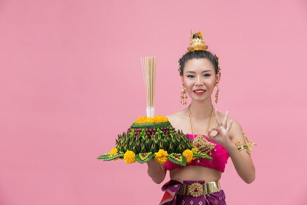 Festival loy krathong; femme en tenue traditionnelle thaïlandaise tenant flottant décoré