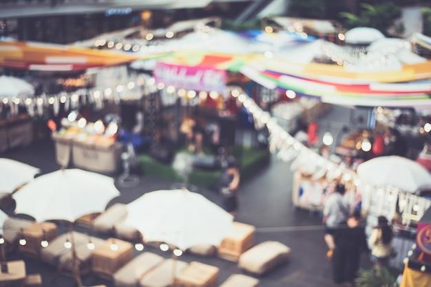 Festival de marché de nuit floue gens marchant sur la route