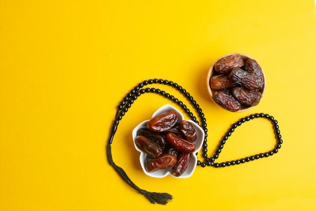 Festival ramadan kareem, dates au bol avec chapelet sur fond jaune