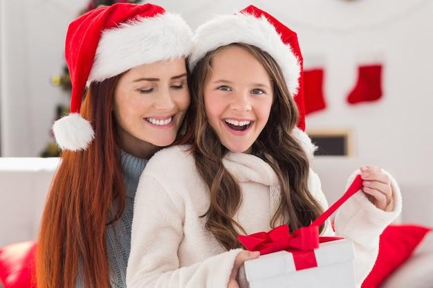 Festive mère et fille sur le canapé avec cadeau
