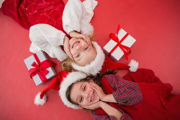 Festive petites filles souriant à la caméra avec des cadeaux