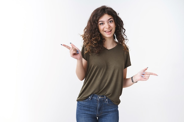 Fêtarde effrontée et mignonne avec des cheveux bouclés portant un t-shirt olive dansant joyeusement vers la gauche droite, différents côtés vous offrent des choix demandant des conseils, prenez une décision, debout sur fond blanc