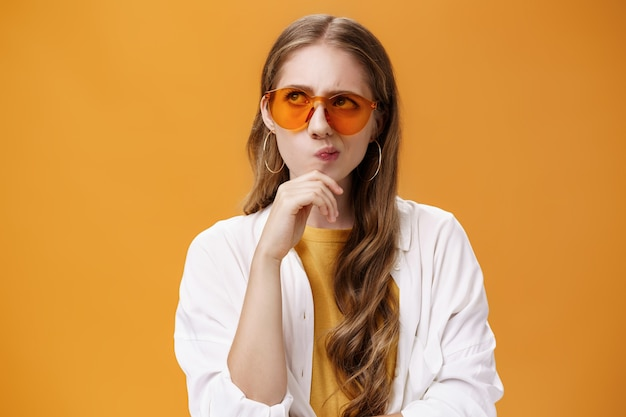 Une fêtarde élégante et réfléchie avec une longue coiffure naturelle ondulée dans des lunettes de soleil à la mode et un chemisier souriant, l'air déterminé au coin supérieur gauche en frottant le menton, pensant posant sur un mur orange.