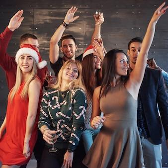 Fête avec des amis. ils aiment noël groupe de jeunes joyeux portant des feux de bengale et des flûtes à champagne dansant dans la fête du nouvel an et l'air heureux. concepts sur la vie en groupe