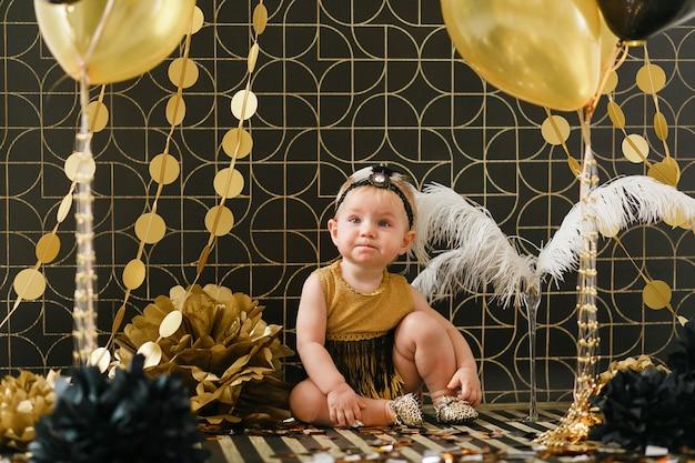 Fête d'anniversaire bébé fille décorée d'un ballon noir et doré.
