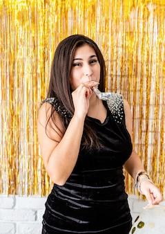 Fête d'anniversaire. belle femme brune en robe de soirée noire célébrant son anniversaire soufflant le générateur de bruit