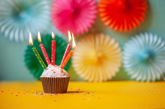 Fête d'anniversaire avec cupcake et bougies colorées.