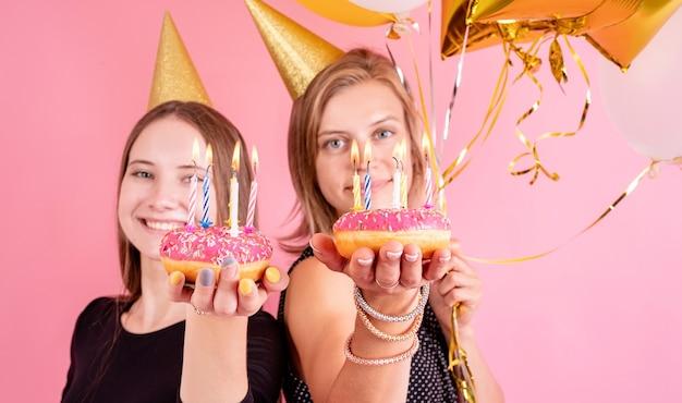 Fête d'anniversaire. deux amies célébrant l'anniversaire portant des chapeaux d'anniversaire d'or tenant des ballons et des beignets roses avec des bougies sur fond rose
