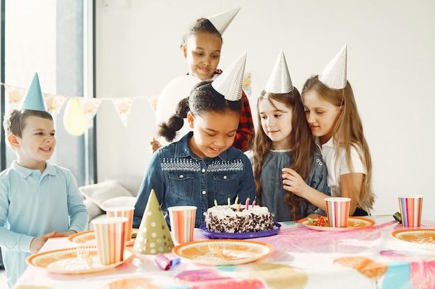 Fête d'anniversaire drôle pour enfants dans une salle décorée. enfants heureux avec gâteau et ballons.