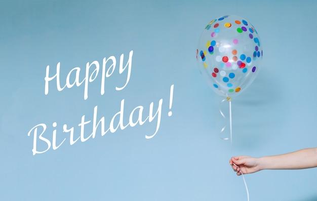Fête d'anniversaire élégante ou vacances avec des ballons se bouchent. main tenant un ballon multicolore