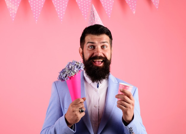 Fête d'anniversaire. homme barbu souriant en chapeau de fête avec bouquet de fleurs.