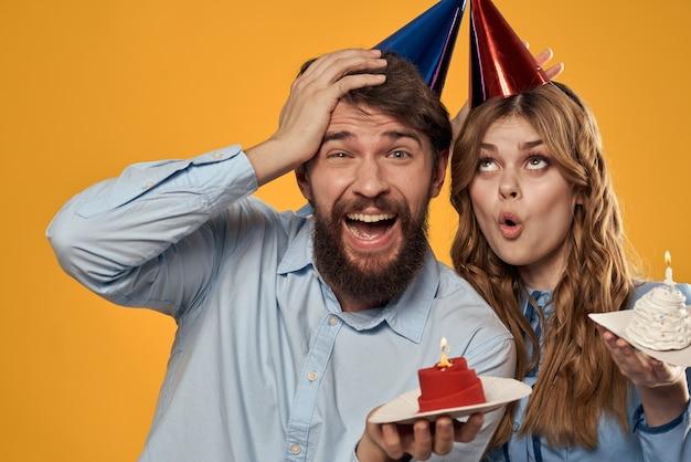 Fête d'anniversaire homme et femme amusant sur mur jaune