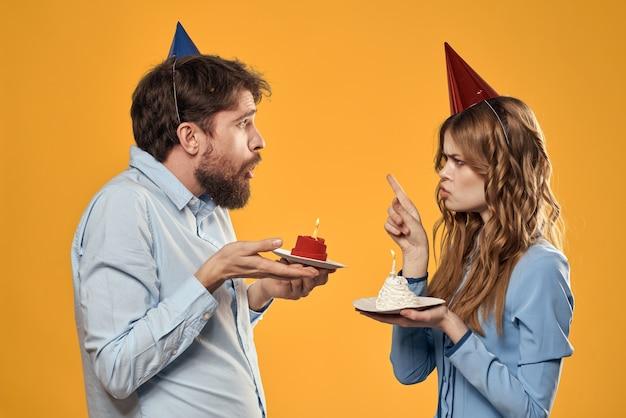 Fête d'anniversaire homme et femme dans une casquette avec un gâteau sur un mur jaune vue recadrée.