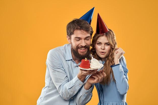 Fête d'anniversaire homme et femme dans une casquette avec un gâteau sur un mur jaune