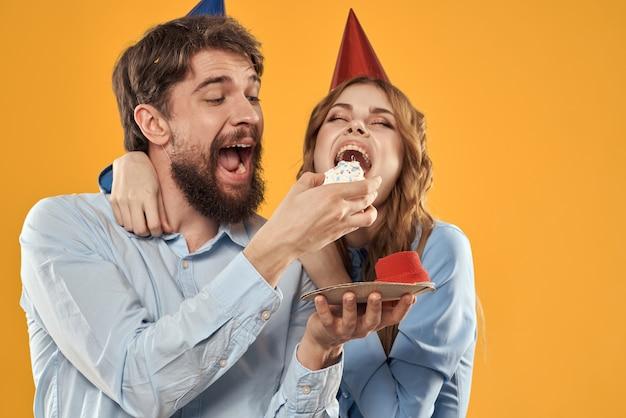 Fête d'anniversaire homme et femme dans une casquette avec un gâteau sur une vue recadrée jaune