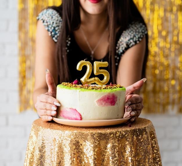 Fête d'anniversaire. jolie femme de race blanche en robe de soirée noire prête à manger le gâteau d'anniversaire célébrant son vingt-cinquième anniversaire