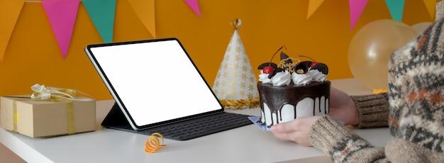 Fête d'anniversaire en ligne avec tablette écran vide, gâteau, chapeau de fête et boîte présente sur tableau blanc