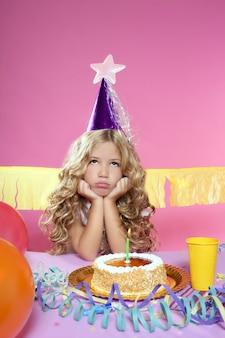 Fête d'anniversaire petite fille blonde s'ennuie avec gâteau aux bougies