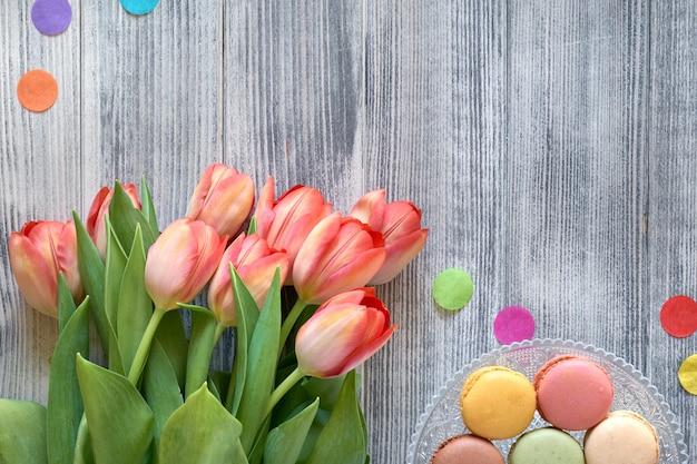 Fête d'anniversaire à plat avec des tulipes et des bonbons orange jn un plateau décoratif sur bois gris texturé