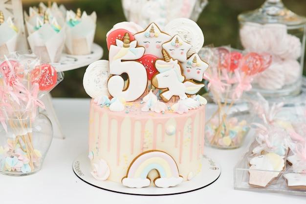 Fête d'anniversaire pour enfants candy bar, blanc et rose, mise au point sélective. gâteau avec une licorne de 5 ans