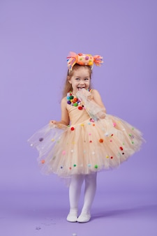 Fête d'anniversaire pour enfants, mascarade. petite fille enfant bambin heureux dans un déguisement de tutu gonflé, s'amuser sur l'espace violet. espace pour le texte