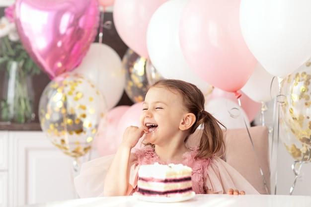 Fête d'anniversaire souriant heureux enfant fille est assise à table sur des ballons manger un gâteau d'anniversaire utiliser la main