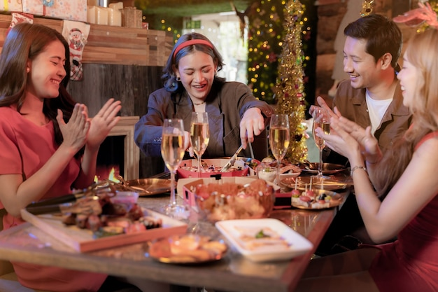 Fête d'un bel ami asiatique féminin et masculin célébrant une femme servant une pizza sur une table