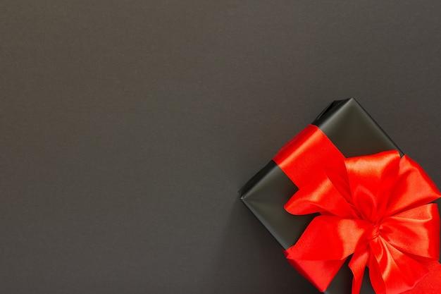 Fête avec cadeau, boîte cadeau noire avec ruban rouge et arc sur fond noir