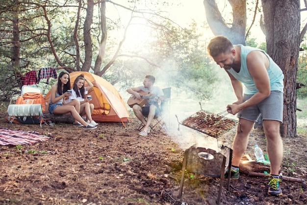 Fête, camping de groupe d'hommes et de femmes en forêt. ils se détendent, chantent une chanson et cuisinent un barbecue