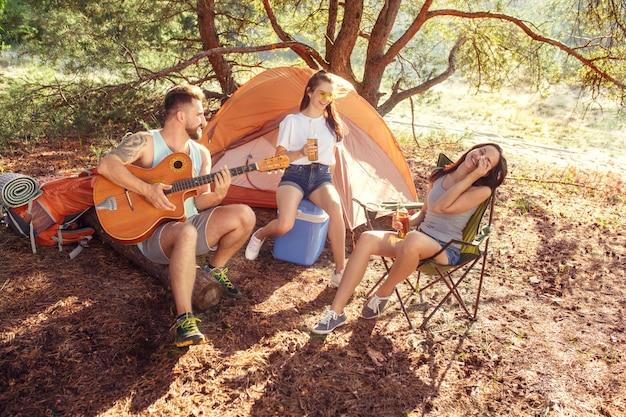Fête, camping de groupe d'hommes et de femmes en forêt. ils se détendent, chantent une chanson