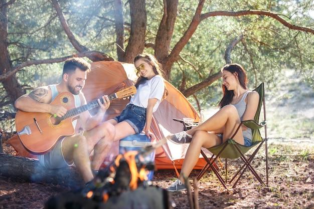 Fête, camping de groupe d'hommes et de femmes à la forêt. ils se détendent, chantent une chanson
